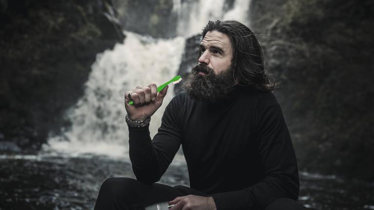 Ein Mann sitzt in der Wildnis und putzt sich vor einem Wasserfall die Zähne. Zahnbürste ist eingefärbt.