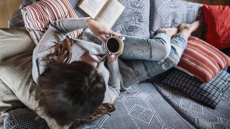 Frau macht es sich mit einer Tasse Kaffee auf dem Sofa gemütlich.