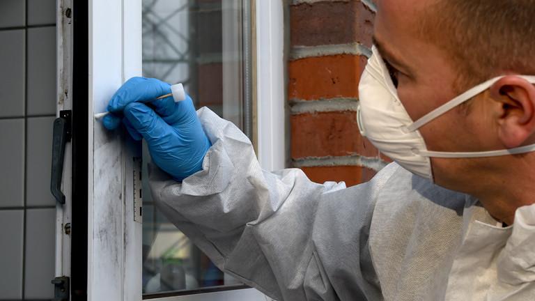 Ein Kriminalbeamter sichert Spuren am Fenster