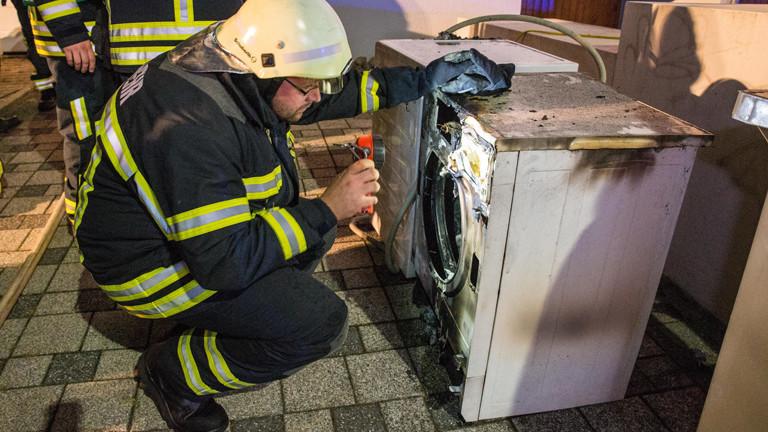 Ein Feuerwehrmann begutachtet einen ausgebrannten Wäschetrockner