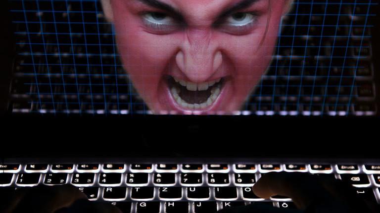 Hasserfülltes Gesicht vor Laptop-Bildschirm
