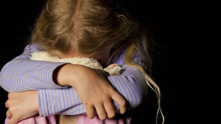 Mädchen vergräbt sein Gesicht in einem Kuscheltier