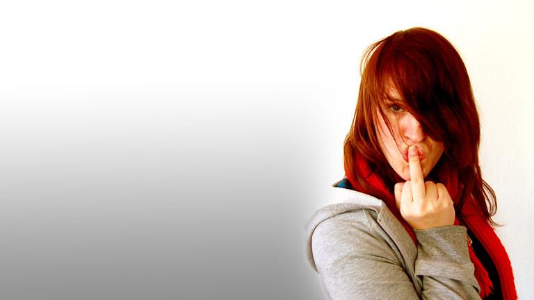 Eine Frau küsst ihren Mittelfinger.