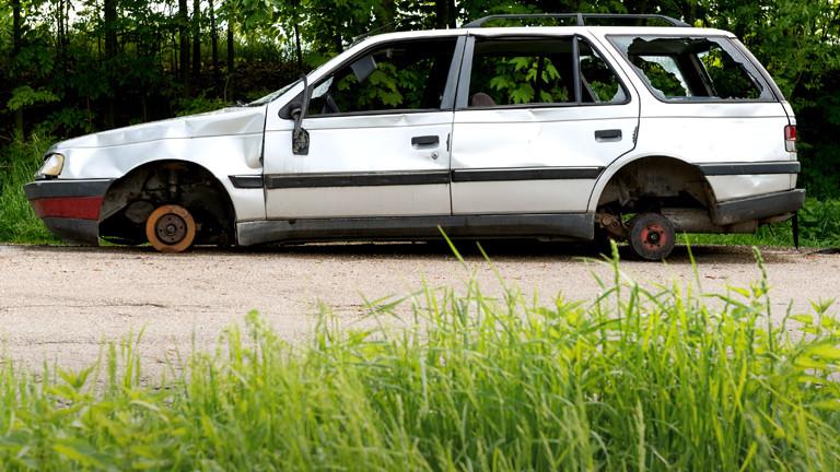 Ein Auto mit eingeschlagenen Scheiben, dem die Räder gestohlen wurden.