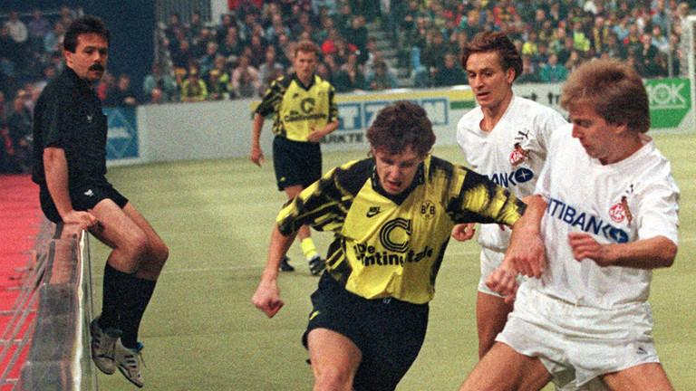 Manfred Führer als Schiedsrichter, flüchtet sich bei einem Bundesliga-Spiel auf die Bande.