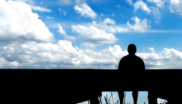 Ein Mann sitzt vor einem See auf einem Steg.