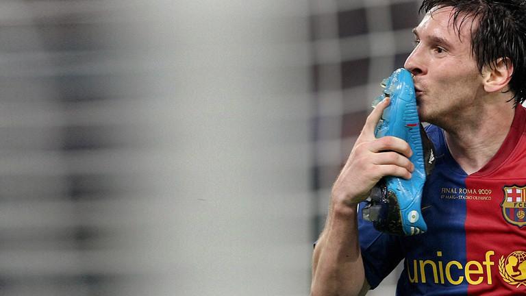 Fußballer Messi küsst seinen Fußballschuh.