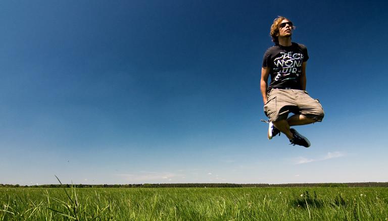 Ein Mann, der im Schneidersitz in die Luft springt.