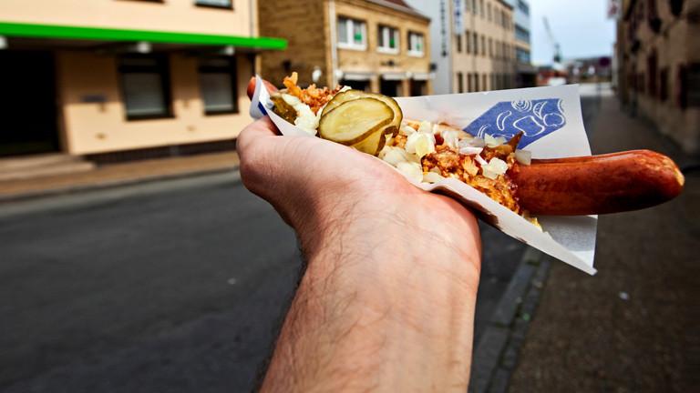 Ein Hotdog in einer Hand.