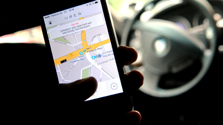 Jemand hält in seiner Hand ein Smartphone, auf dem die Uber-App aufgerufen ist.