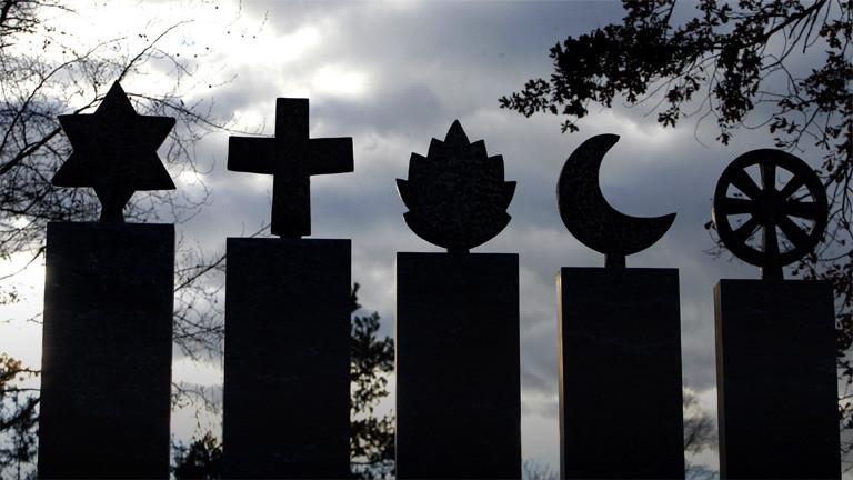 Die Symbole der Religionen Judentum, Christentum, Hinduismus, Islam und Buddhismus aus Stein gehauen nebeneinander.