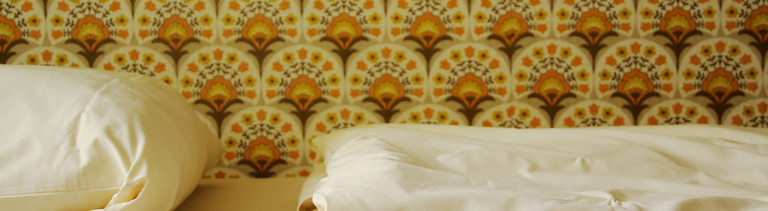 Frisch bezogenes weißes Bett vor Retrotapete.