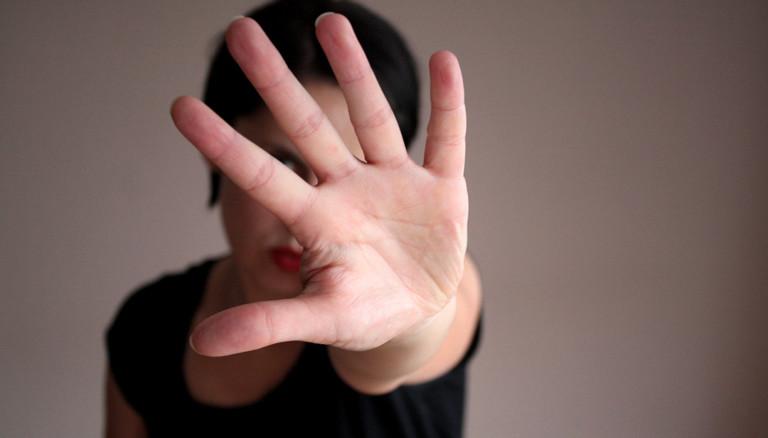 """Frau, die eine Hand ausstreckt, so als wollte sie """"Stop"""" sagen."""