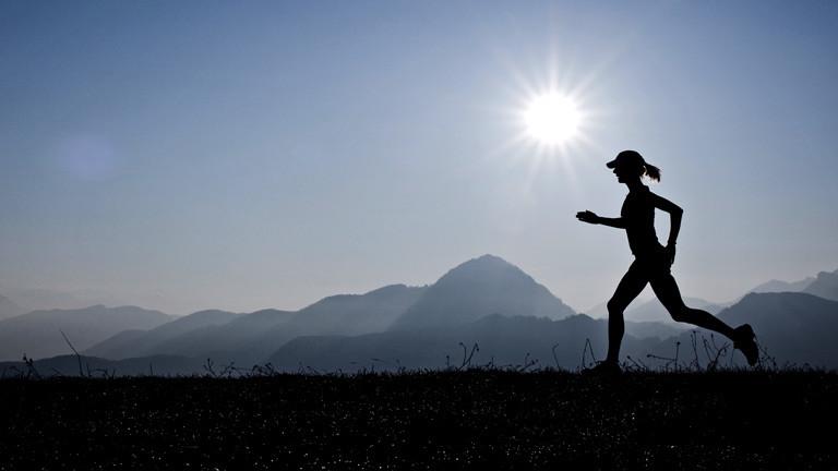 Eine Frau läuft vor einem Bergpanorama bei strahlender Sonne.