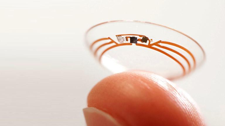 Eine spezielle Kontaktlinse von Google, gehalten von einem Finger