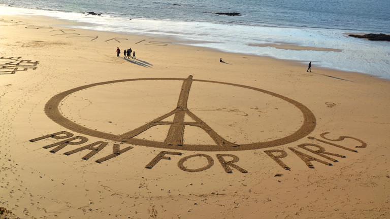 """In den Sand an einem Strand ist ein Peace-Symbol mit Eiffelturm gemalt. Dazu die Worte """"Pray for Paris""""."""