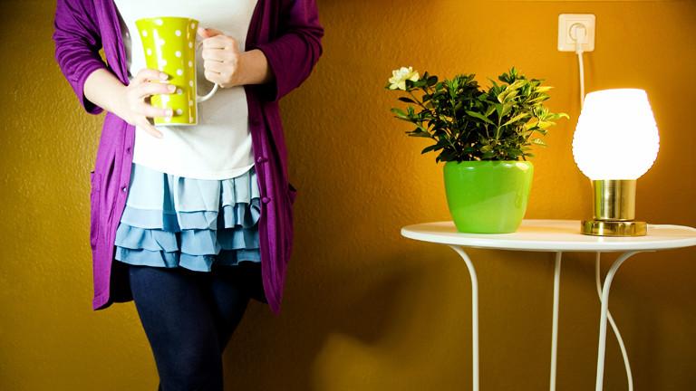 Ein Frauenkörper mit Kaffee in der Hand, auf einem Tisch eine Blume und eine leuchtende Lampe.
