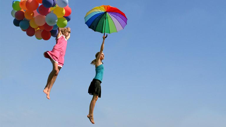 Zwei Frauen fliegen an Luftballons und mit Regenschirm