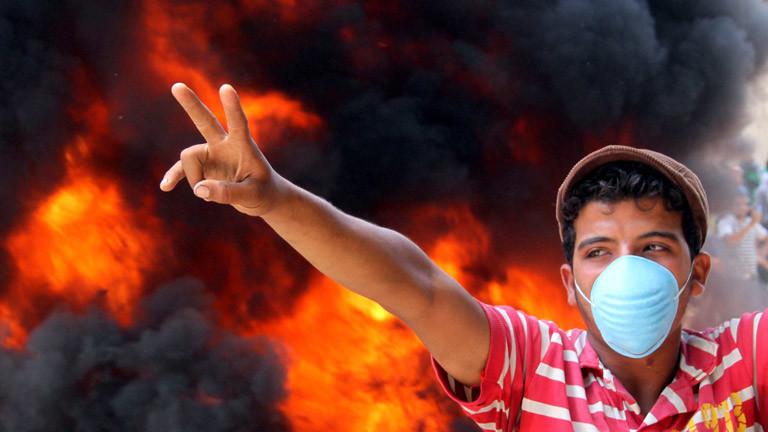 Ein junger Mann vor Flammen auf dem Tahrir-Platz in Ägypten