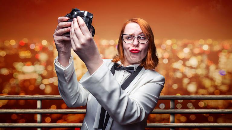 Eine Frau im Smoking zieht eine Selfiegrimasse