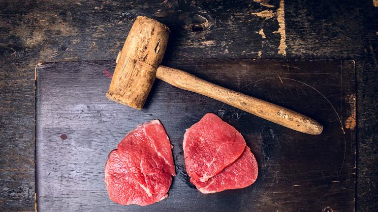 Zwei rohe Kalbsschnitzel mit Hammer