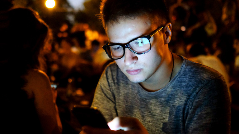 Ein junger Mann schaut auf sein Handy