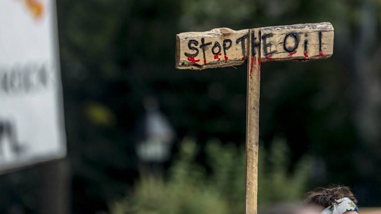 """Ein Schild mit der Aufschrift """"Stop the Oil"""""""