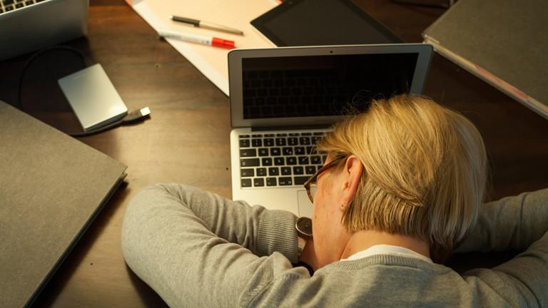 Frau legt Kopf auf die Arme und schläft am Schreibtisch