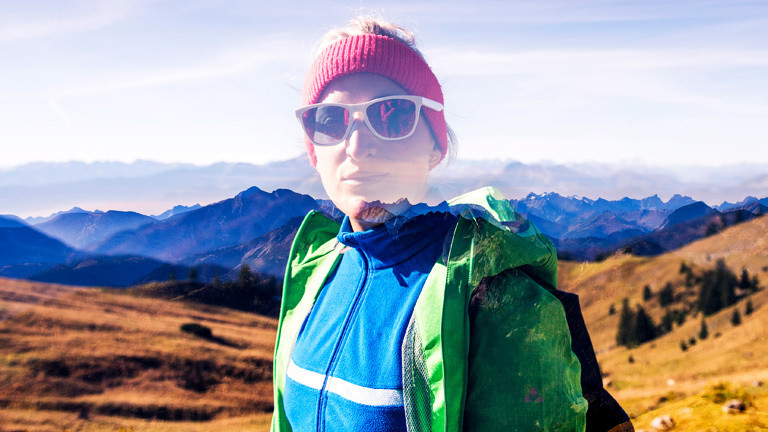 Frau in Outdoorkleidung vor Bergkulisse