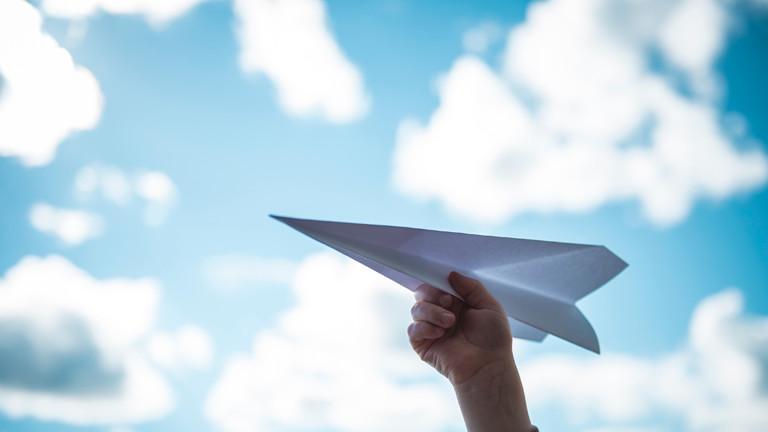 Hand, die einen Papierflieger hält