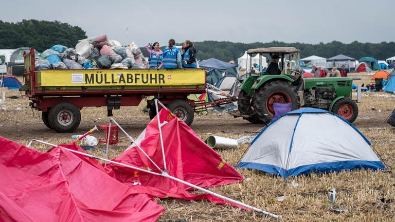 Ein Trecker mit Anhänger sammelt Müll nach dem Hurricane-Festival ein