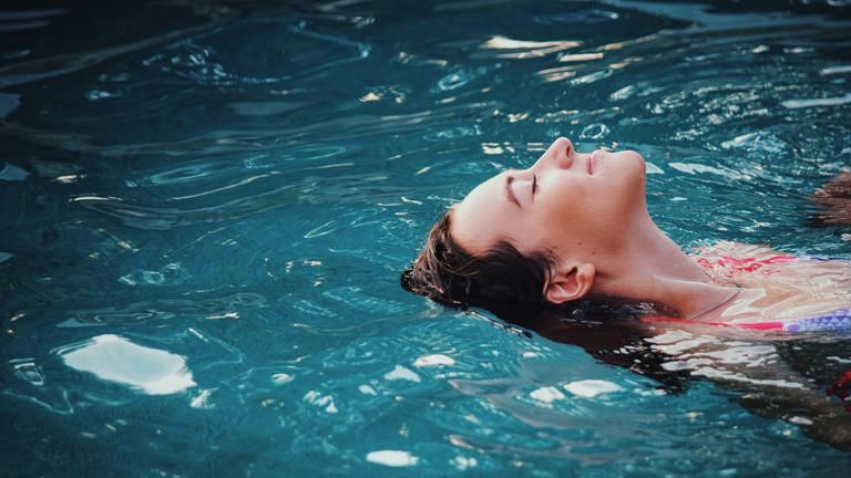 Frau liegt mit geschlossenen Augen auf dem Rücken in einem Swimmingpool.