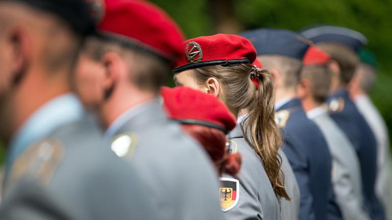 Bundeswehrsoldaten und -soldatinnen in einer Reihe, Rückenansiicht.