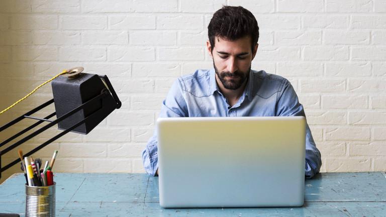 Mann an Laptop im Büro