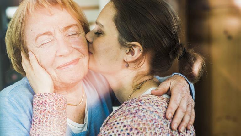 Junge Frau küsst ältere Frau auf die Wange