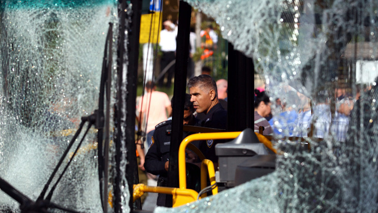 An Israeli policeman inspects the scene after a terrorist attack on a bus in central Tel Aviv, Israel, 21 November 2012.