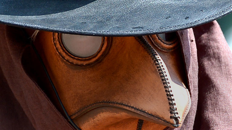 Ein Mann trägt ein Pestmaske. Mit solchen Masken wurden früher Menschen behandelt, die an der Pest erkrankt sind.