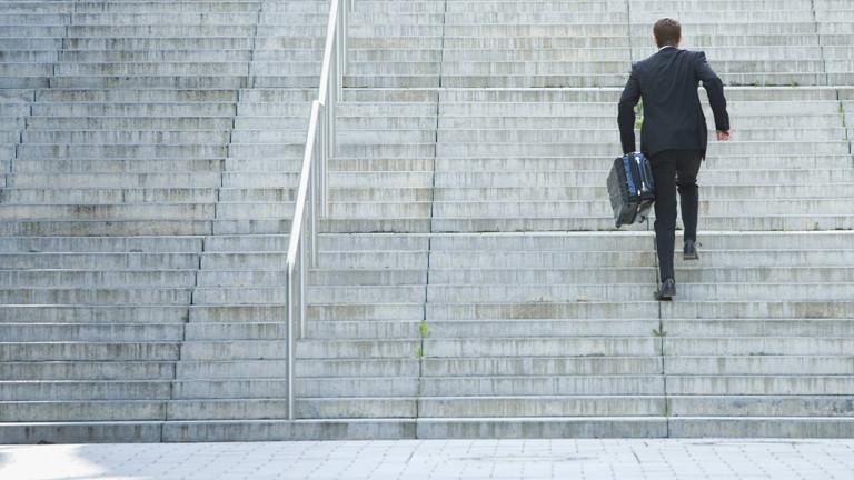 Mann im Anzug rennt mit Koffer eine Treppe hinauf