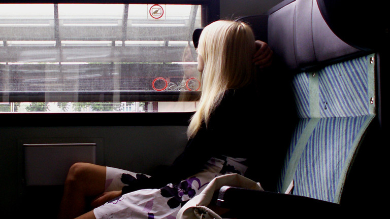 Eine Frau sitzt in einem Zug am Fenster.