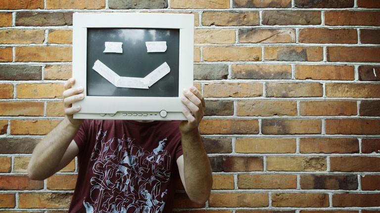 Eine Person hält sich einen Bildschirm vor den Kopf, auf dem ein Gesicht zu sehen ist.