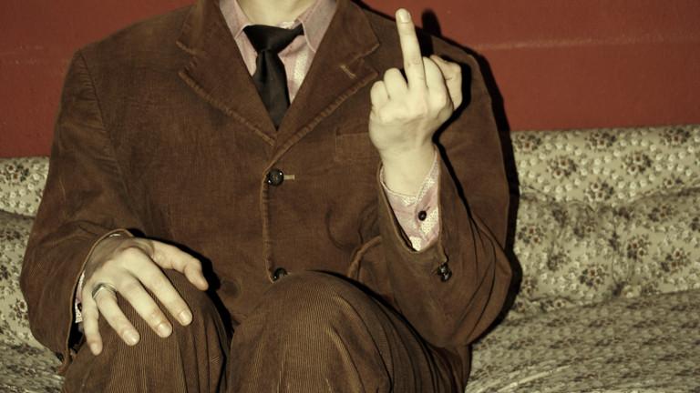 Anzugträger mit erhobenem Mittelfinger