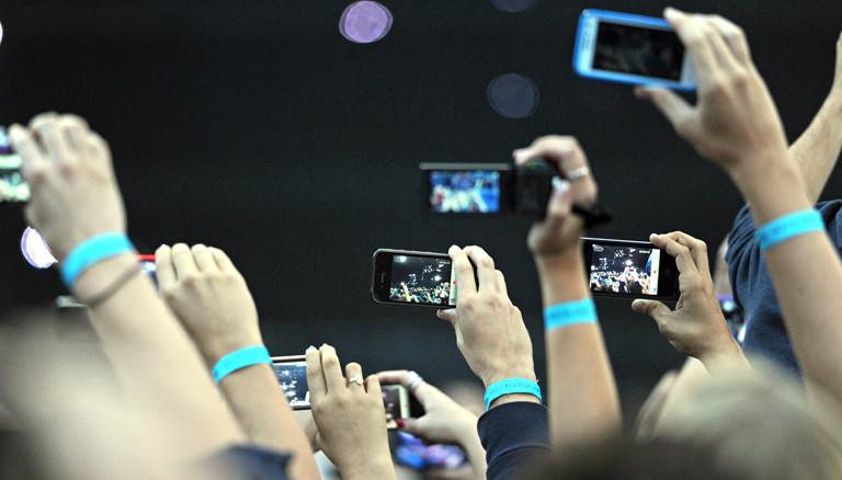 Menschen auf einem Konzert von David Guetta, die mit Handys filmen