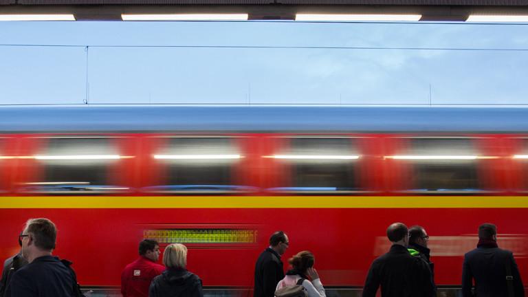 Menschen im Bahnhof, Zug fährt vorbei