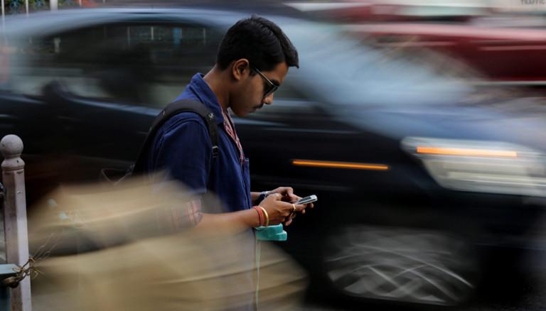 Indischer Hipster auf der Straße mit Smartphone