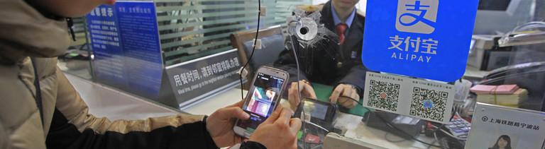 Kundin in einem chinesischen Supermarkt zahlt bargeldlos via Alipay.