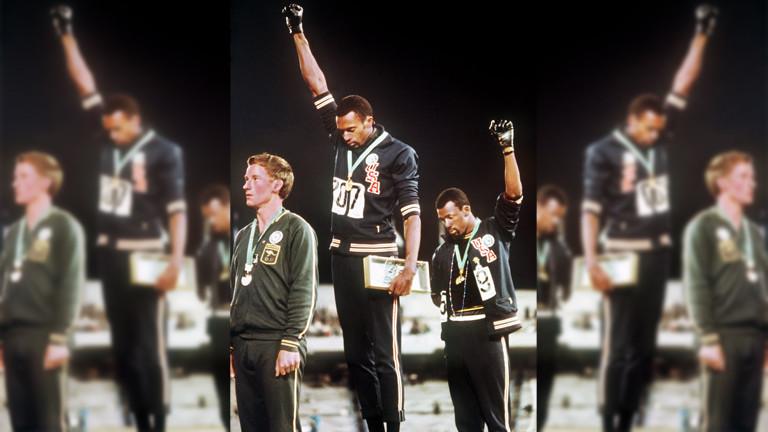"""Bei der Siegerehrung für den 200-m-Lauf der Männer demonstrieren die Amerikaner Tommie Smith (M, Goldmedaille) und John Carlos (r, Bronzemedaille) mit hochgereckter geballter Faust in schwarzem Handschuh für die """"Black Power""""-Bewegung. Links der Gewinner der Silbermedaille"""
