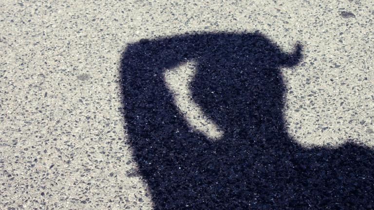 Der Schatten eines Mannes, der sich Schweiß von der Stirn wischt