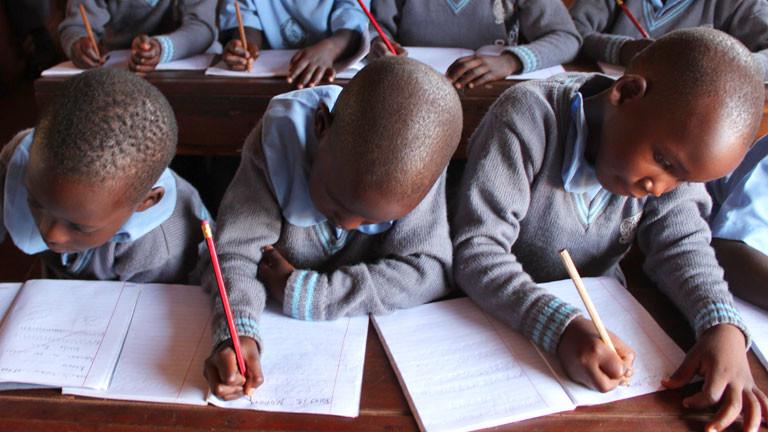 Kinder sitzen auf einer Schulbank und schreiben in Hefte.