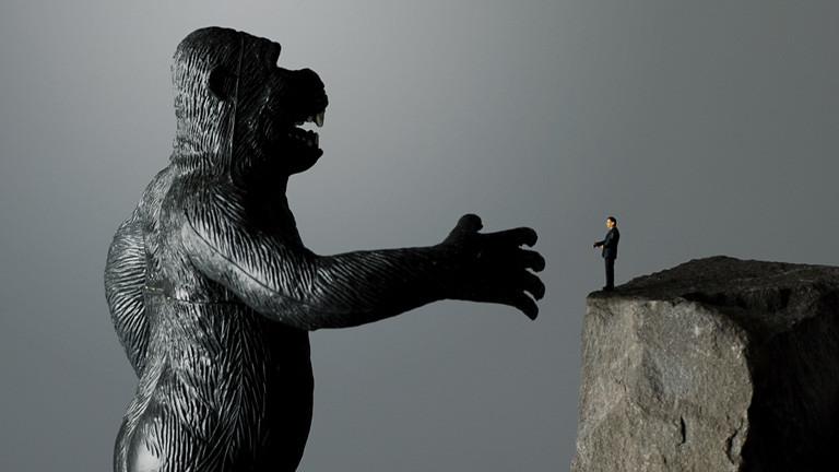 Affe reicht Spielzeugmännchen die Hand