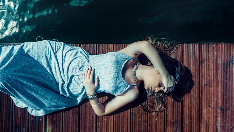 Frau liegt am Wasser auf einem Steg und schläft in der Sonne.